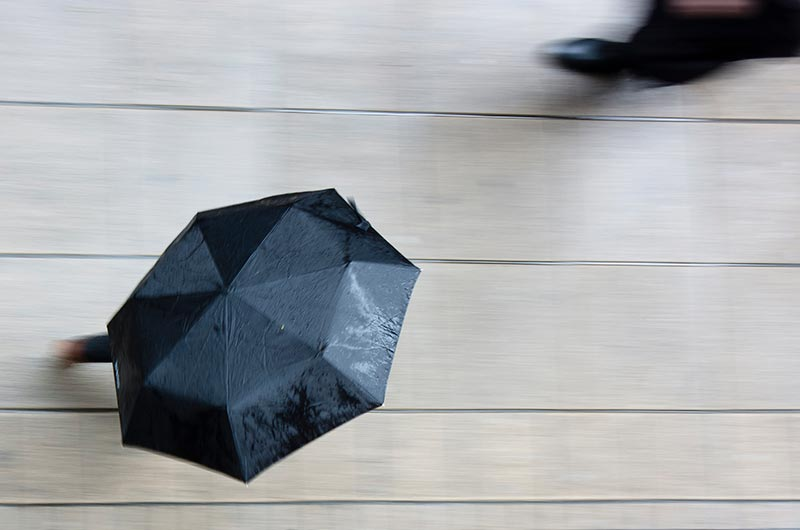 Person Hiding Under an Umbrella