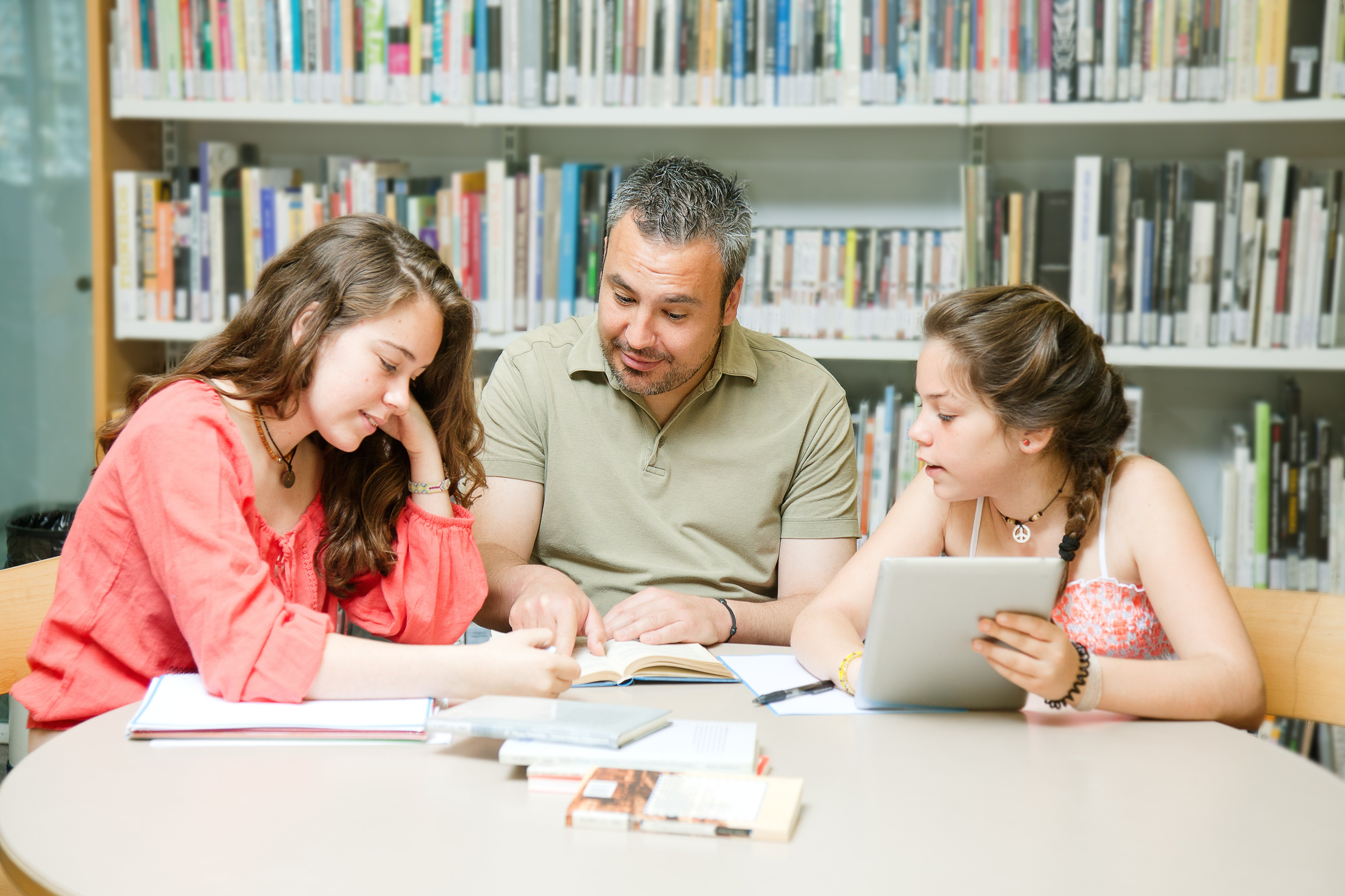 Dad Helping daughters with homework, thinking about saving for retirement and college