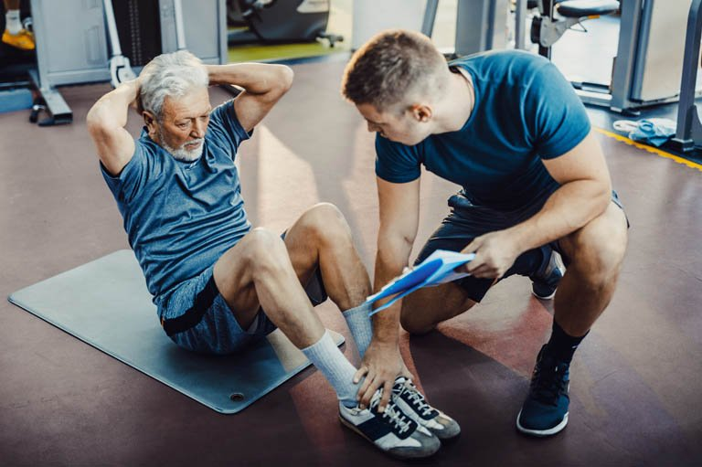 Personal trainer helping senior