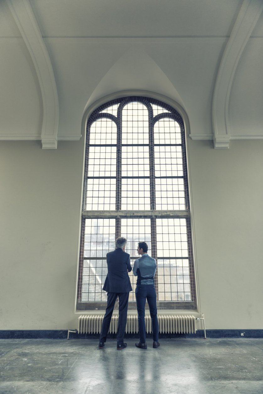 two people standing and talking in front of a tall window
